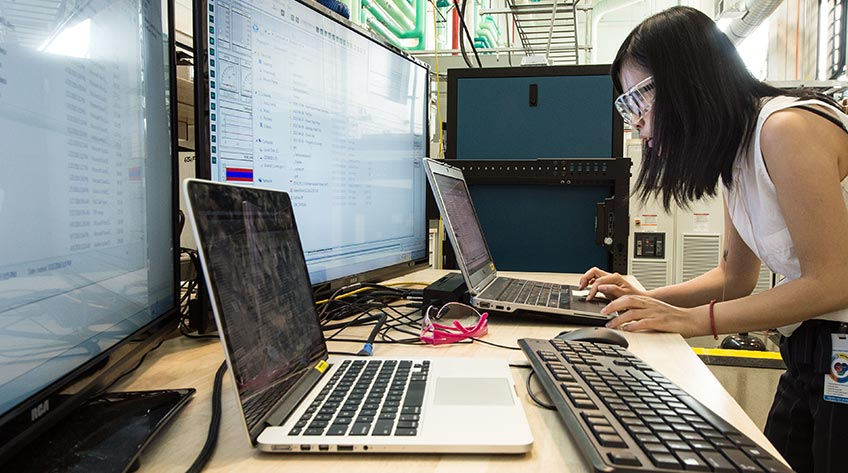 Photo of NREL researcher Fei Ding wearing protective eyewear while working on a computer in a laboratory.