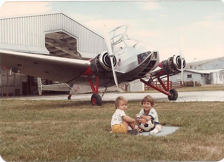 Photo of two young children sitting in grass in front of an airplane outside of a hangar.