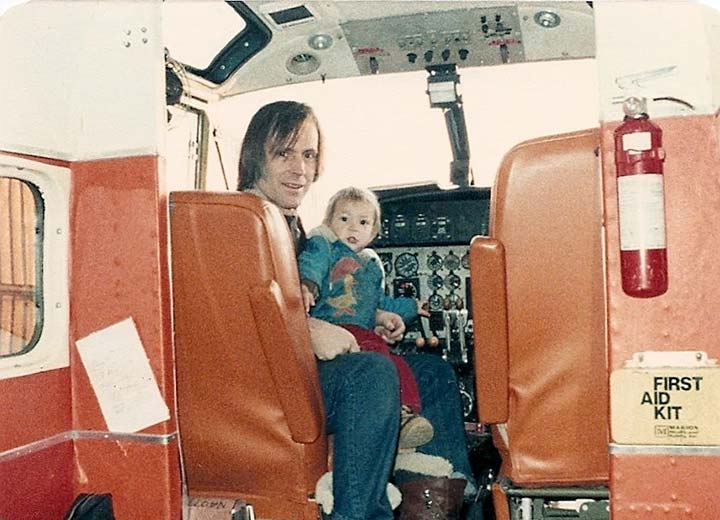 A child sitting on a man's lap in the cockpit of an airplane.