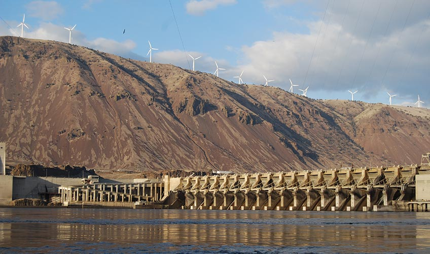 Photo of a hydropower plant with wind turbines situated atop mountains in the background.