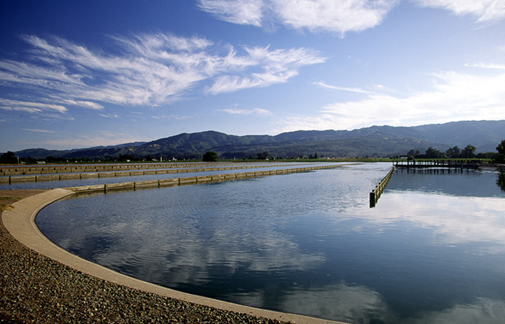 Photo of a large water resource recovery pond with clouds reflected in it, mountains in the background, and cloud-filled sky above.