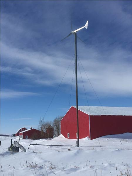 A photograph of a red barn with a small, distributed wind turbine in the foreground.