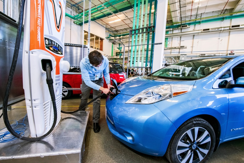 An NREL researcher plugs a blue electric car into a charging port.