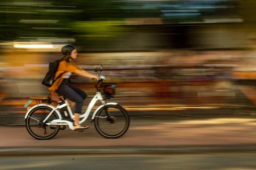 Photo of person riding bike in city setting.