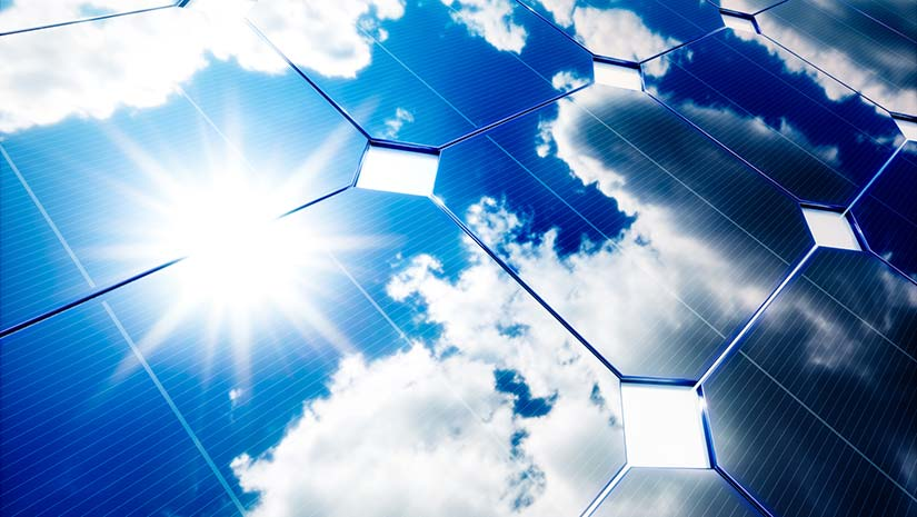 Photo of a close-up view of a solar panel with sun and blue skies in the reflection.