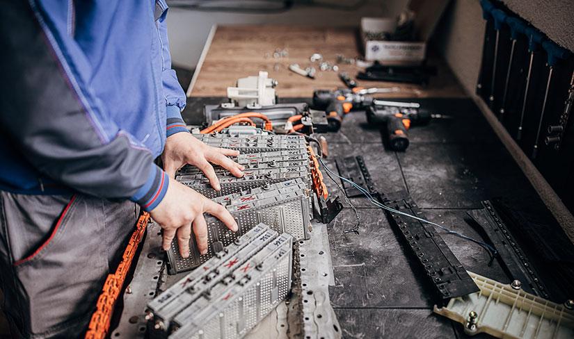 整備士の工房のテーブルに置かれた電気自動車のリチウムイオン電池の写真。
