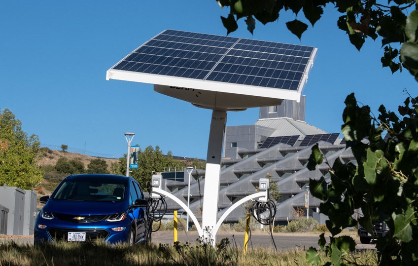 An electric vehicle charges at a port with an integrated solar panel in front of an NREL building.