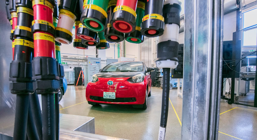Image of an electric vehicle inside a laboratory. High-powered charging cables are in the foreground.