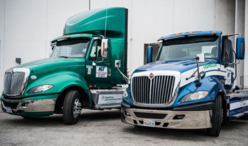 Two heavy duty semi trucks, one green and one blue, are parked next to each other.
