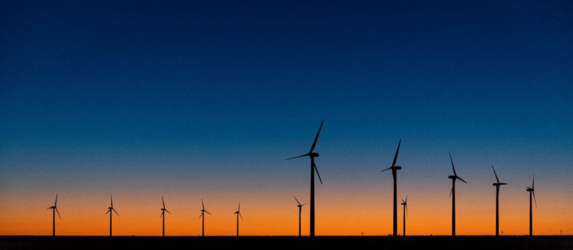 Photo of two rows of wind turbines at sunset.