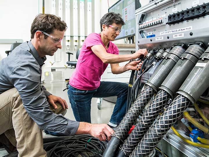 NREL researchers work on the Consolidated Utility Base Energy (CUBE) System in the Energy Systems Integration Facility at NREL.