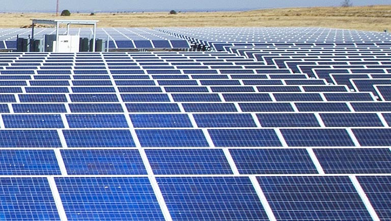 An image shows a large field of solar photovoltaic panels.