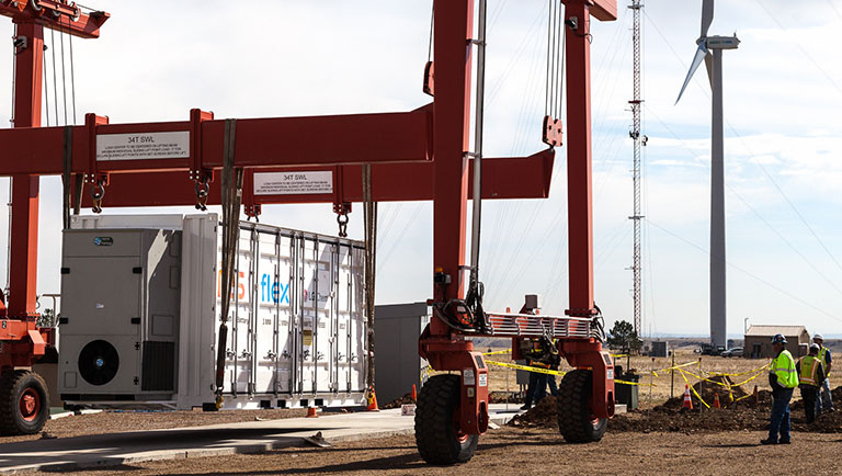 An image shows a large battery system, housed inside a shipping container, begin lowered onto a concrete pad by a red crane. A wind turbine from the National Wind Technology Center appears in the background.