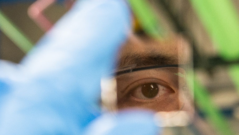 A researcher holds up a highly reflective perovskite wafer between his fingers. The fingers and background are out of focus, but the reflection of his eye in the wafer is sharp.