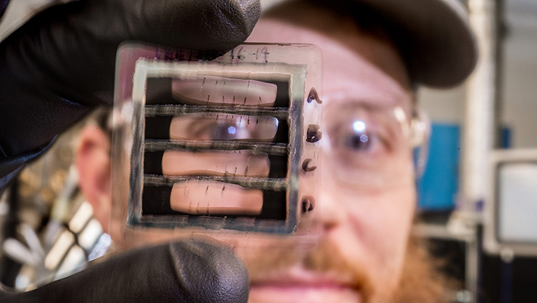 NREL researcher Matt Reese holds up a glass substrate with strips of opaque thin film solar cells removed, so you can see parts of his face through the resulting holes.