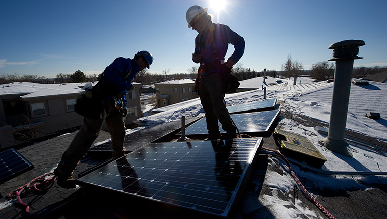 Two solar installers secure solar panels on the roof of a residential structure.