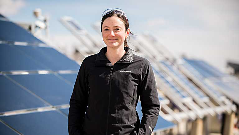 NREL scientist Adele Tamboli, co-author of a recent article on silicon-based multijunction solar cells, stands in front of an array of solar panels.