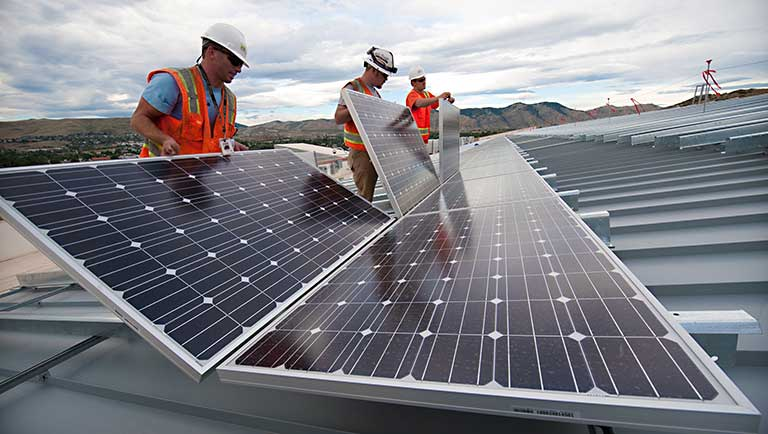 Installers place solar panels on the roof of a commercial building.