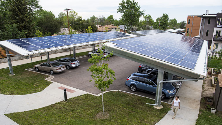 A carport at a senior living facility is covered in solar panels.