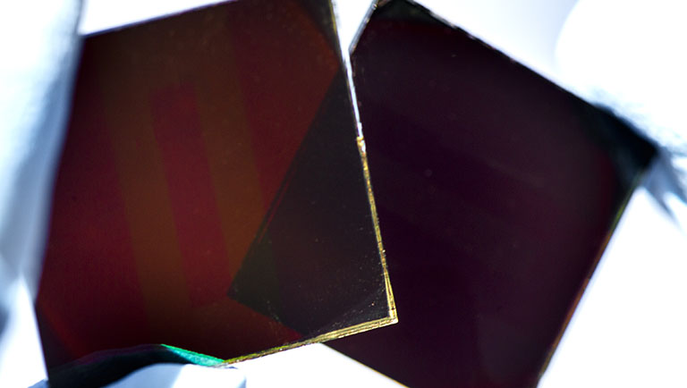 An NREL researcher holds up two glass squares coated in a thin film material.