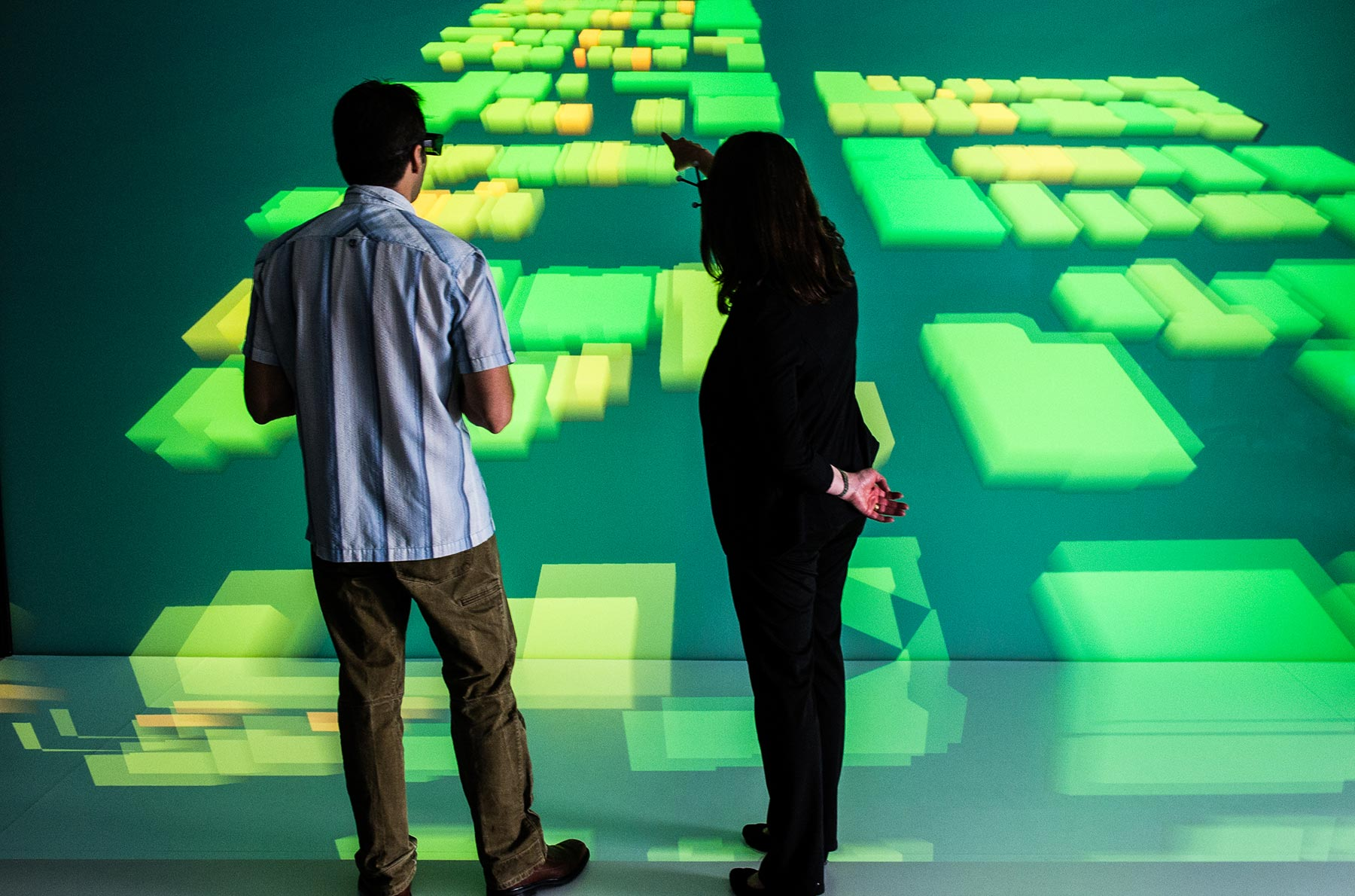 Photo of two people in Insight Center Visualization Room at the National Renewable Energy Laboratory looking at a community energy grid model.