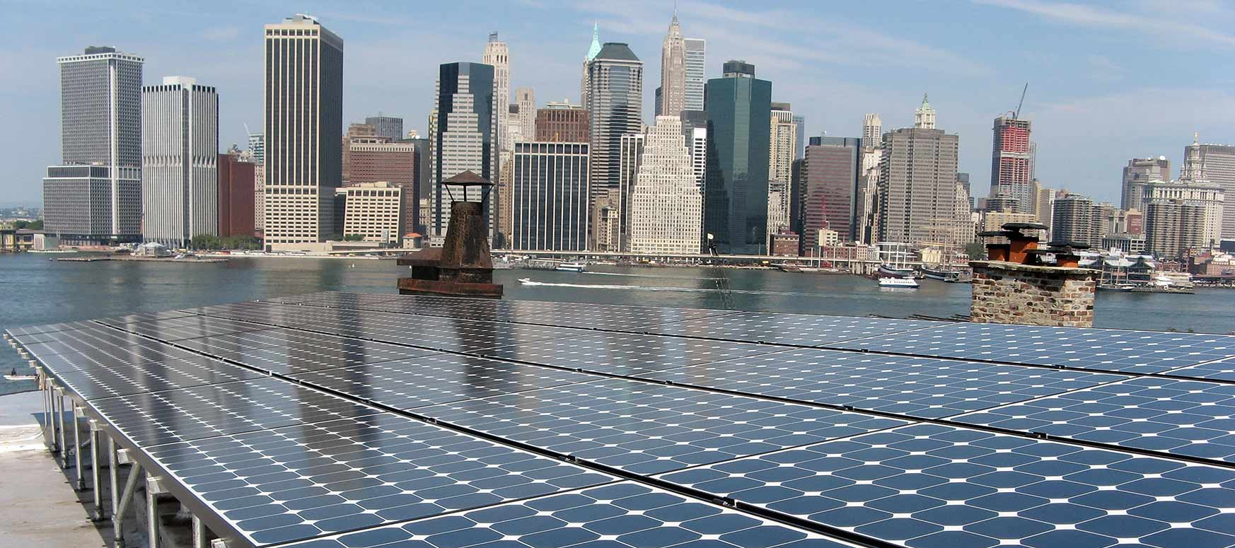 Photo of a photovoltaic array, harbor and New York City skyline