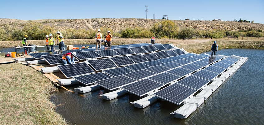 Workers install solar panels on water.