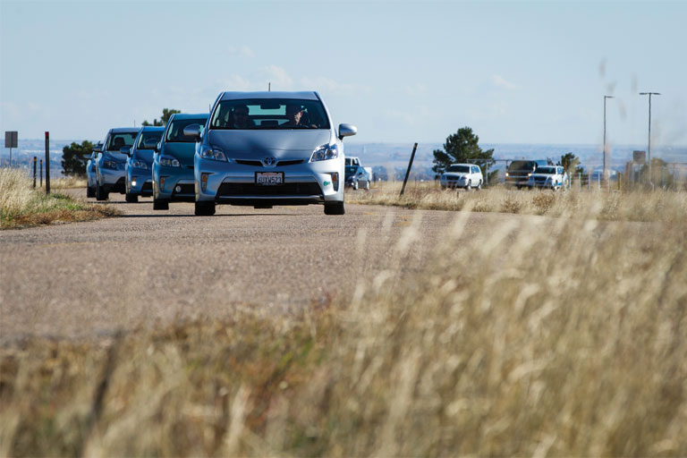 Photo of reporters test driving Toyota prototype electric and fuel cell vehicles.
