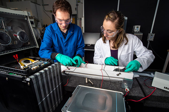 Two researchers work on a relithiation reactor, a chemical bath used to replenish batteries, in NREL's Energy Systems Integration Facility, Materials Characterization Lab.