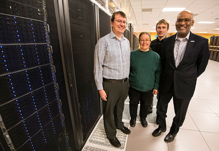 Four researchers pose in front of NREL's Eagle supercomputer.