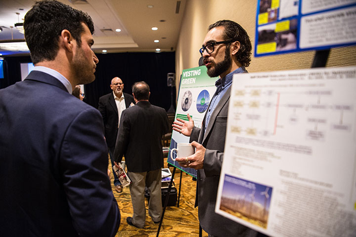 A researcher explains his poster to a participant at Emerging Markets Day at the Industry Growth Forum in Denver, Colorado.