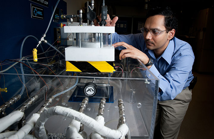 A researcher works on equipment in NREL's Advanced Power Electronics Lab.