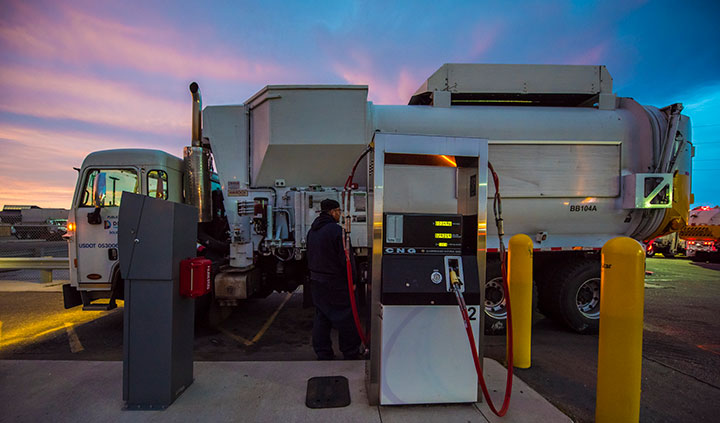 A worker at the City and County of Denver Platte Facility fuels a garbage truck with compressed natural gas.