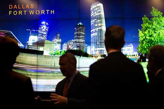 Photo of four people standing near an image of the Dallas-Fort Worth skyline.