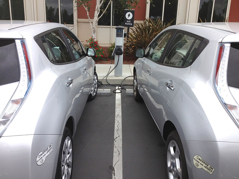 Photo of two silver vehicles parked nose-in next to each other in parking spaces in front of brick building and plugged into a shared silver and black electric vehicle charging unit.