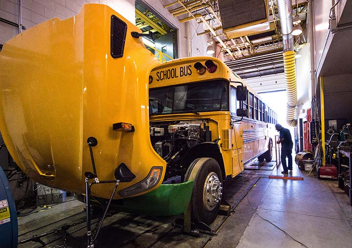 A research technician works on an electric school bus at the ReFUEL laboratory.