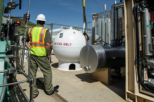 Two men in hard hats supervise installation of a natural gas storage tank.