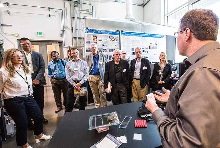 A researcher explains internal short circuit research to USCAR directors on a tour of the ESIF at NREL