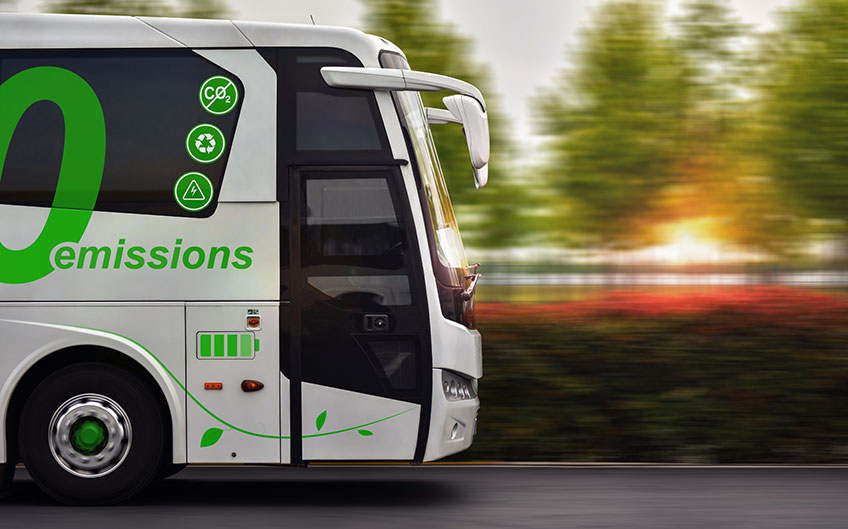 A zero-emission electric bus drives with a green background.