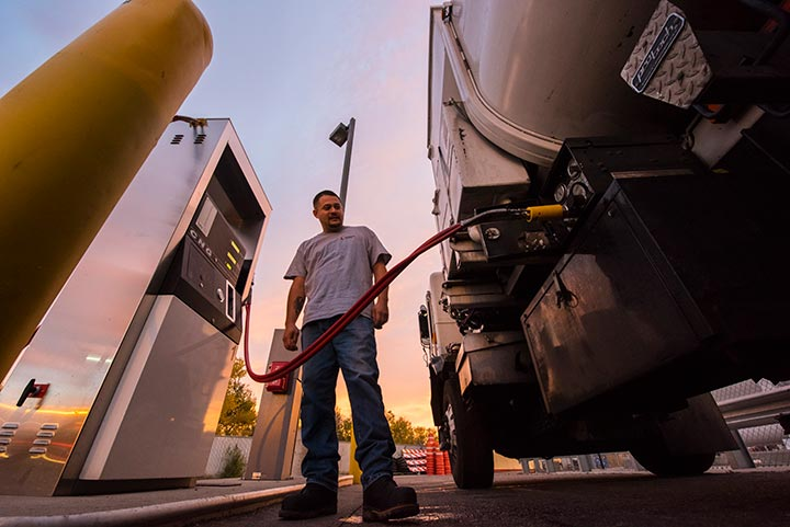 Man at a fuel pump filling a garbage truck with compressed natural gas fuel.