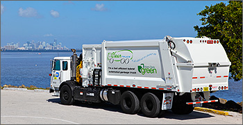 Photo of garbage truck with view of lake and city in background.