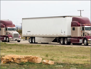 Photo of two tractor trailer trucks driving in close proximity.