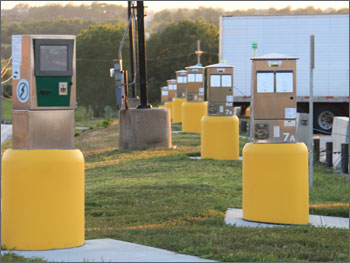 Photo of series of truck stop electrification pedestals near highway with heavy-duty truck parked in the background.