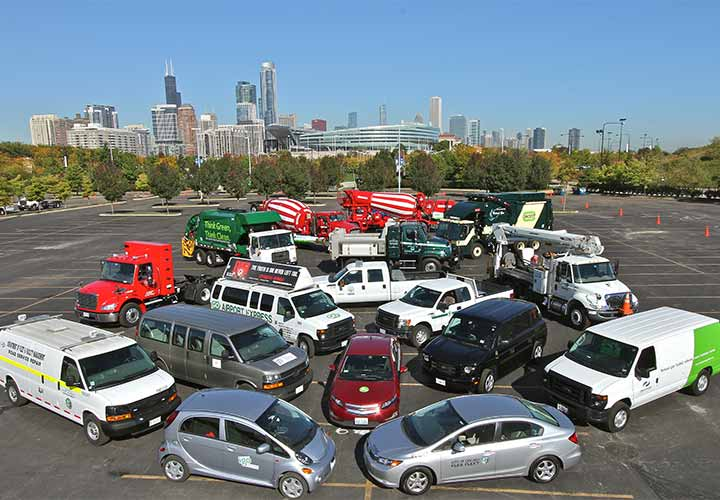 Photo showing multiple alternative fuel vehicles, from sedans to vans, to heavy-duty trucks, with the Chicago skyline in the background.