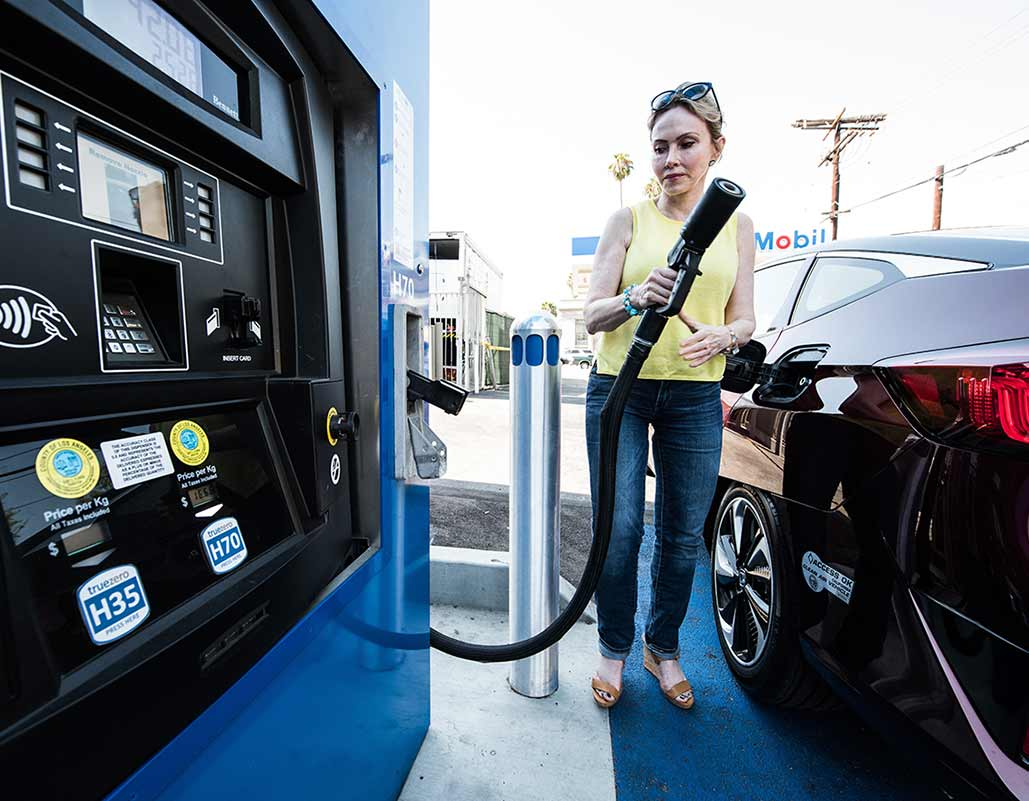 Photo of a woman holding a fuel hose near a hydrogen fuel cell pump and a fuel cell electric vehicle