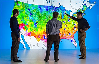 Photo of researchers looking at a large, colorful map of the United States.
