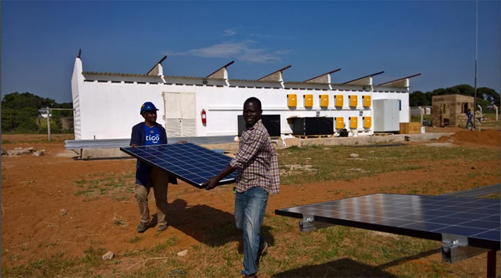 Two men carry a solar panel to place on an array assembly.