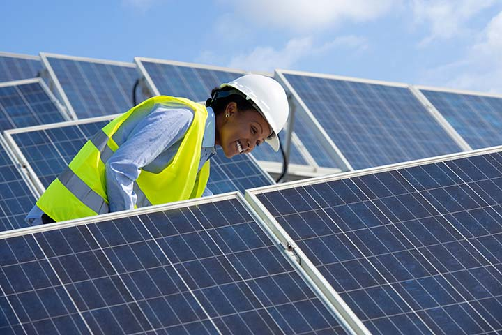 Female in a yellow safety vest and hard hat smiling next to solar photovoltaic panels.