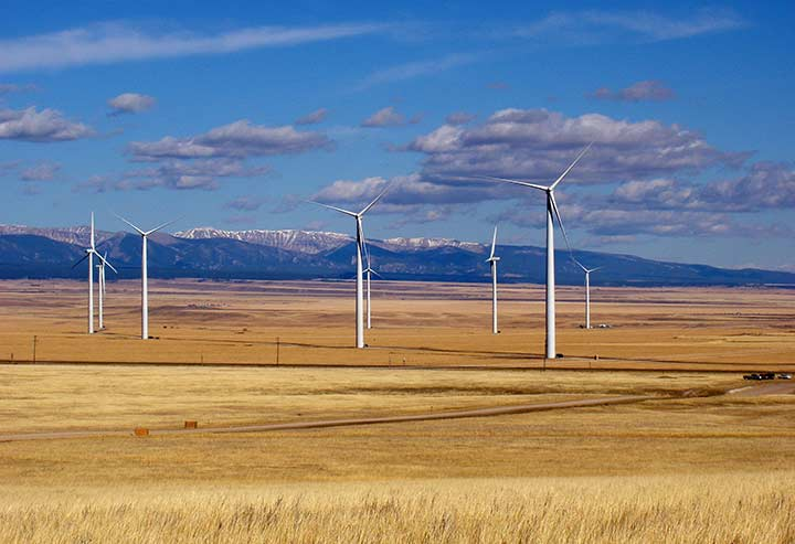 Multiple wind turbines on a flat landscape with mountains in the back.