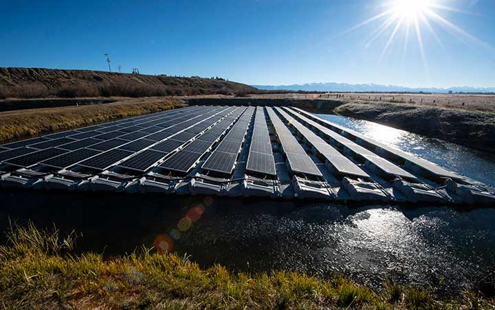 Floating photovoltaic panels laid out across a body of water on a sunny day.